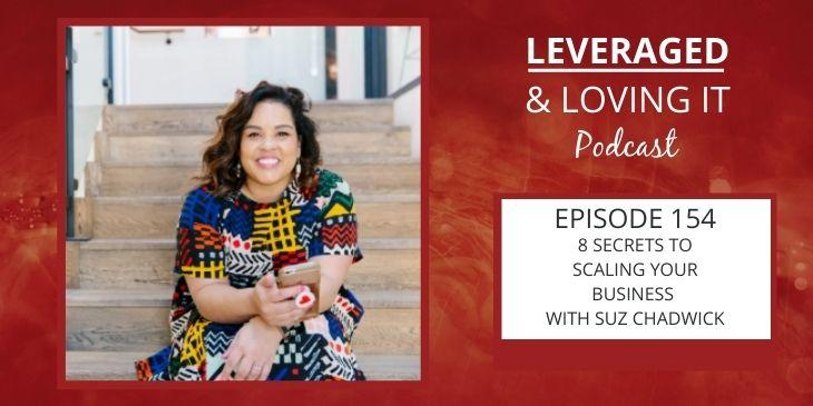 Leveraged and Loving It Episode 154 Suz Chadwick A woman with curly hair sits on some steps smiling at the camera and wearing a very colourful print dress