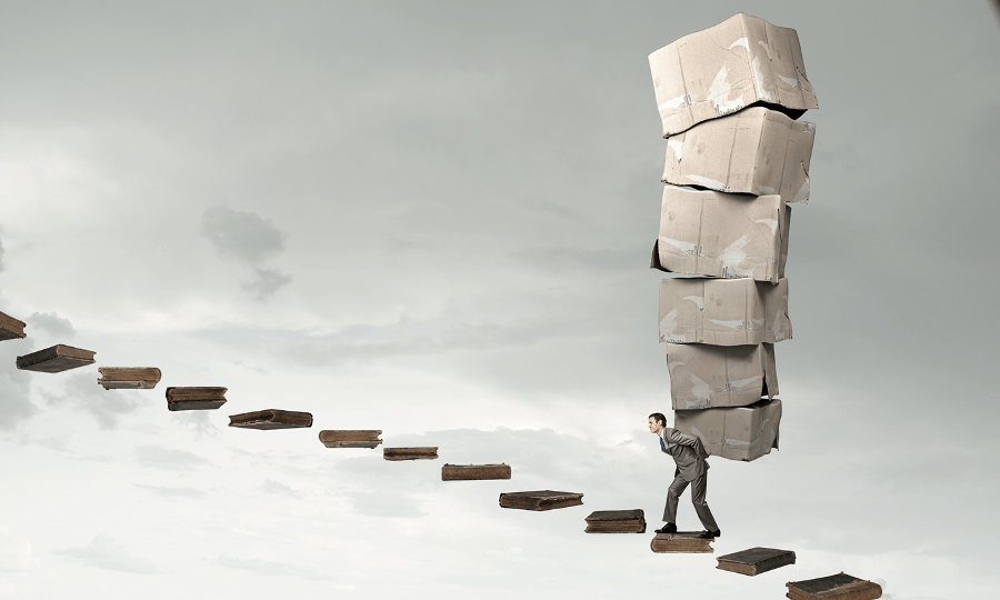 An image of a masc person in a suit, carrying boxes on their back, climbing a floating staircase with grey sky in the background.