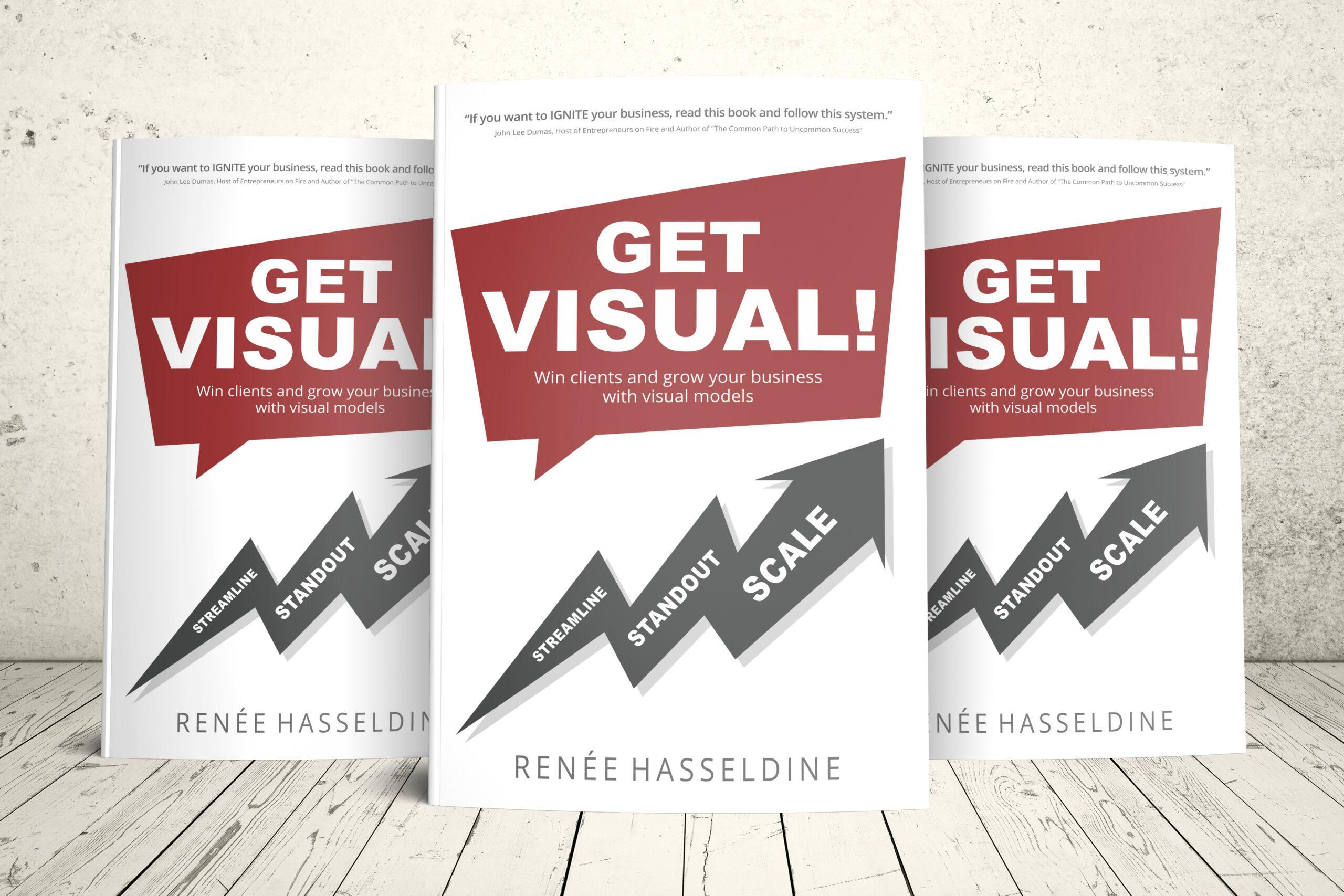 Three copies of GET VISUAL! All lined up on white floorboards, standing up.